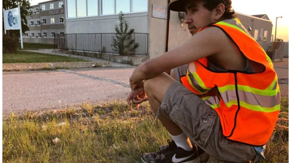 Un adolescent vêtu de gilet orange vif assis sur une pierre près de la rue.