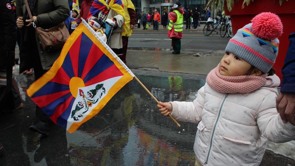 Un enfant qui tient un drapeau du Tibet.