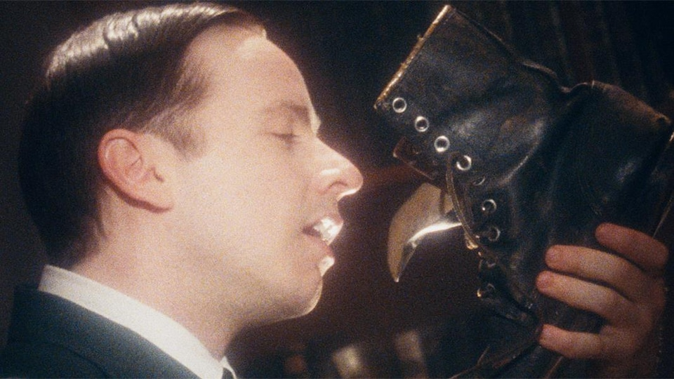 Un homme s'apprête à embrasser une botte en cuire.