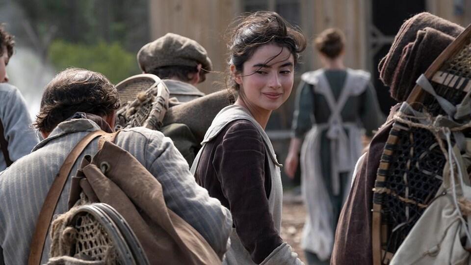 L'actrice Sara Montpetit regarde des personnages marchant derrière elle.
