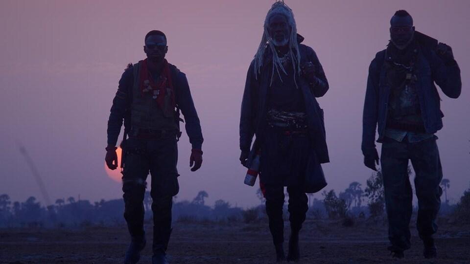 Trois personnes marchent dans un milieu désert.