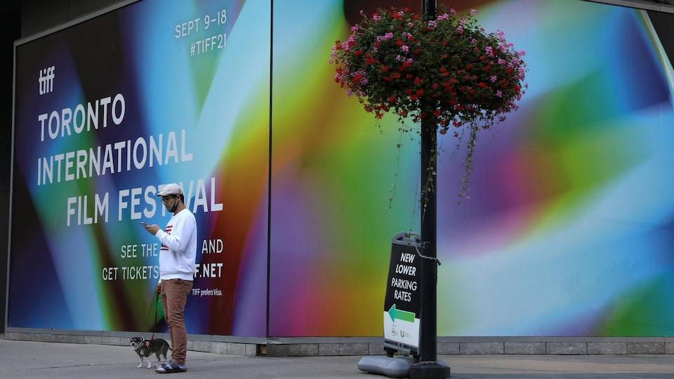 Un homme qui fait marcher son chien consulte son téléphone devant le TIFF Bell Lightbox, qui est le quartier général du Festival international du film de Toronto.