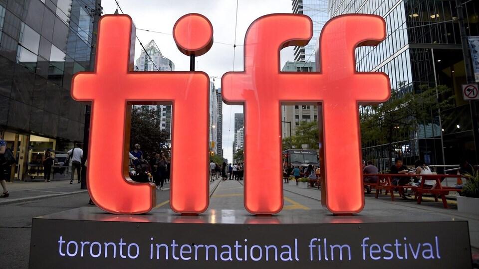 Des lettres géantes T i f f sur un piédestal.