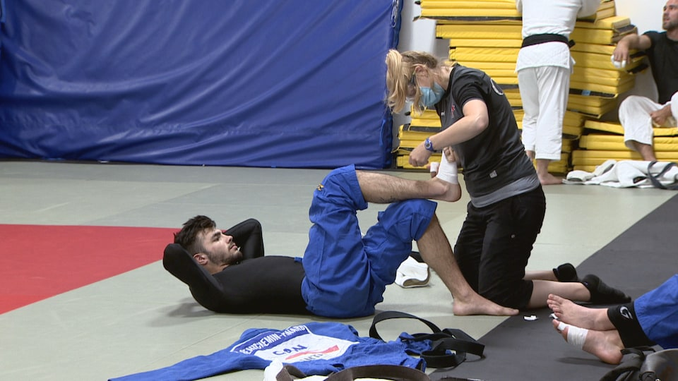 Tiffany Hunting, thérapeute en chef, pose un bandage sur le pied d'un judoka allongé sur le tatami.