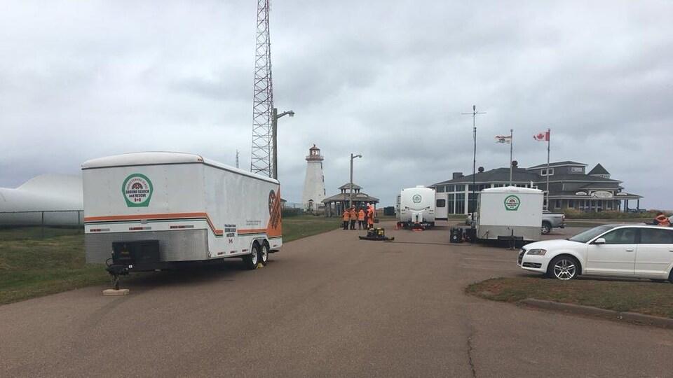 Quelques secouristes se concertent près de trois roulottes contenant leur matériel.