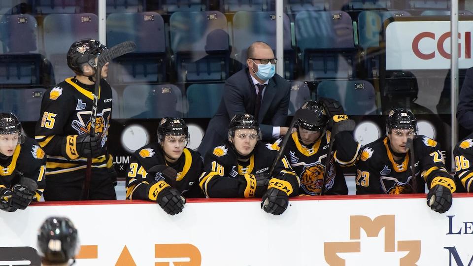 Un entraîneur de hockey avec un masque derrière ses joueurs au banc.