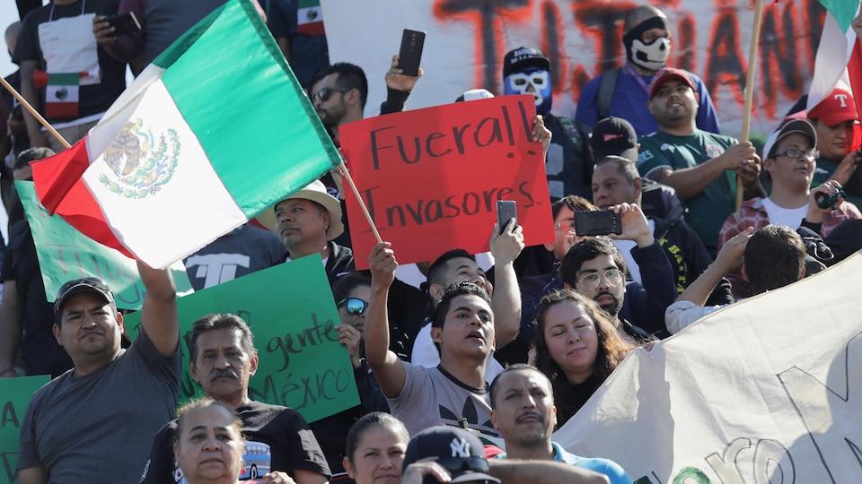Des gens en groupe brandissent des drapeaux mexicains et des affiches anti-migrants.