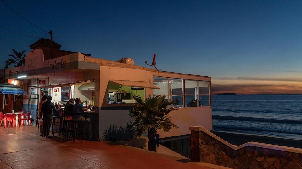 Des clients dans un bar, qui donne sur une plage à Tijuana au Mexique.