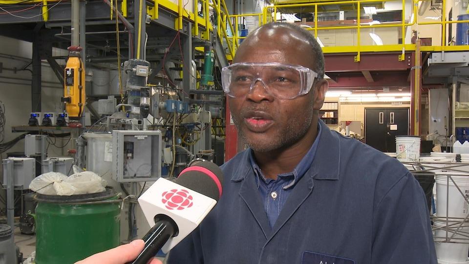 Un homme portant de l'équipement de protection dans une usine accorde une entrevue au micro.