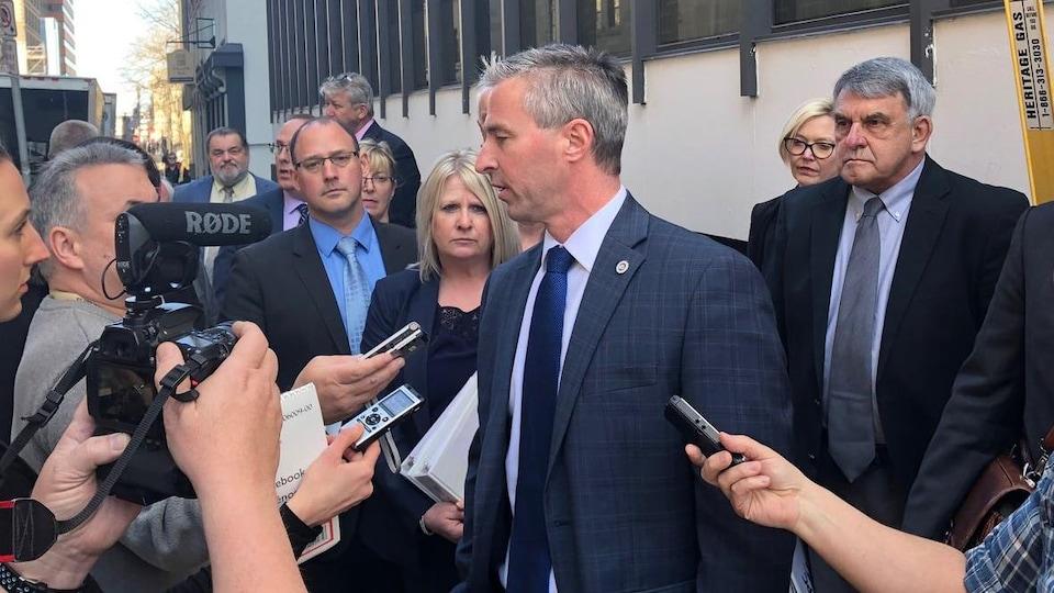 Tim Houston sur le trottoir près de Province House, entouré de membres des médias, le 27 mars 2019 à Halifax.