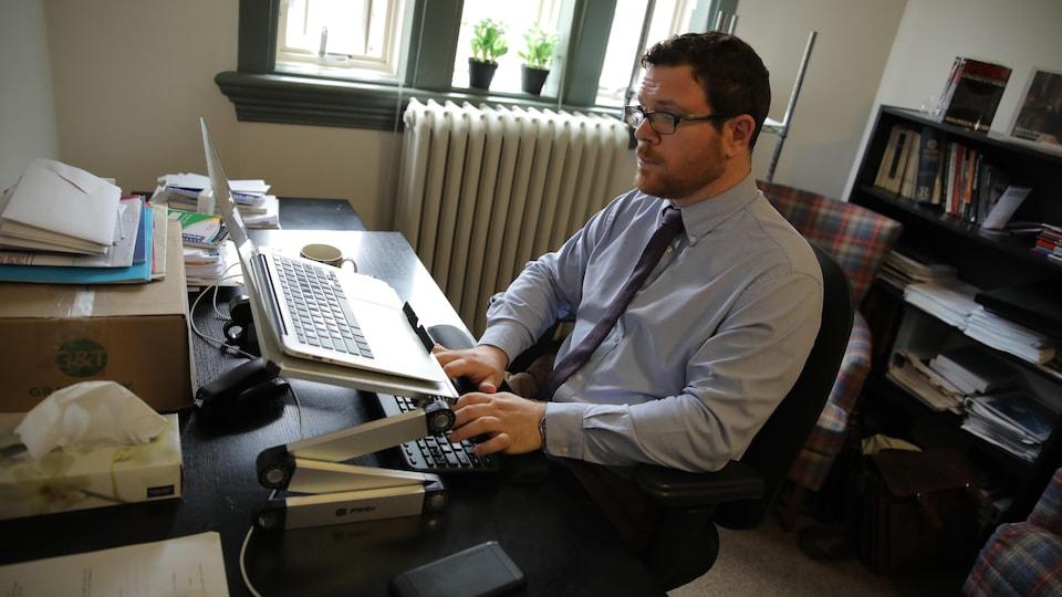 Tim McSorley est assis dans son bureau devant son ordinateur portable ouvert et près d'une fenêtre.