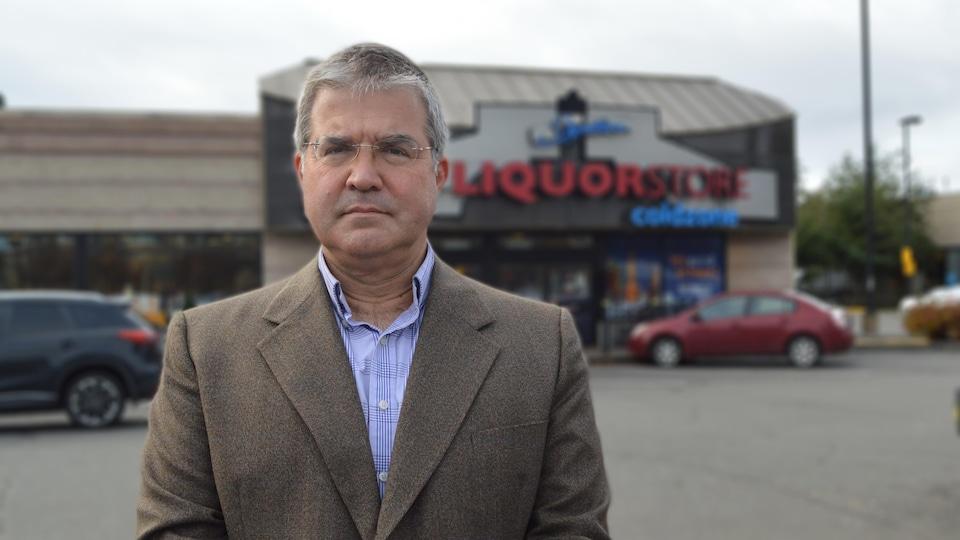 Un homme se tient debout devant un magasin de vente d'alcool, BC Liquor Store.