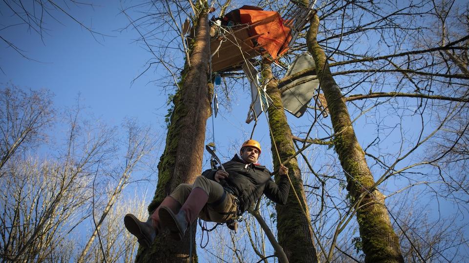 Un homme portant un casque suspendu à une corde se balance sous sa tente installée au sommet de trois arbres.