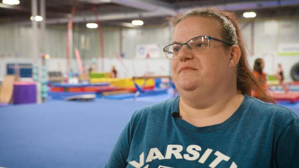 Tina Caderma, la fondatrice en pleine entrevue avec Radio-Canada dans un gymnase avec des filles qui pratique en arrière-plan.