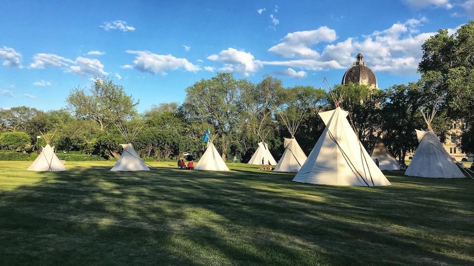 Sept tipis dansun parc, la coupole du palais législatif de Regina est en arrière plan.