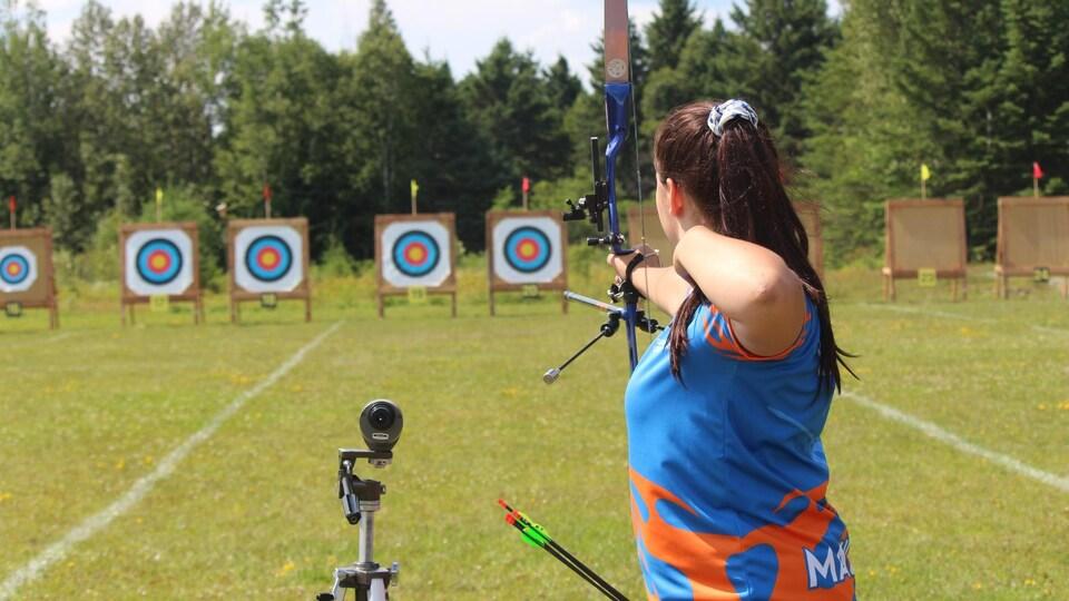 Une athlète de tir à l'arc vise une cible.