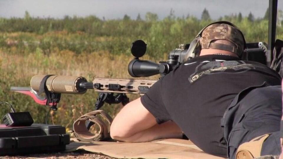 Un tireur d'élite militaire vise une cible avec son fusil.