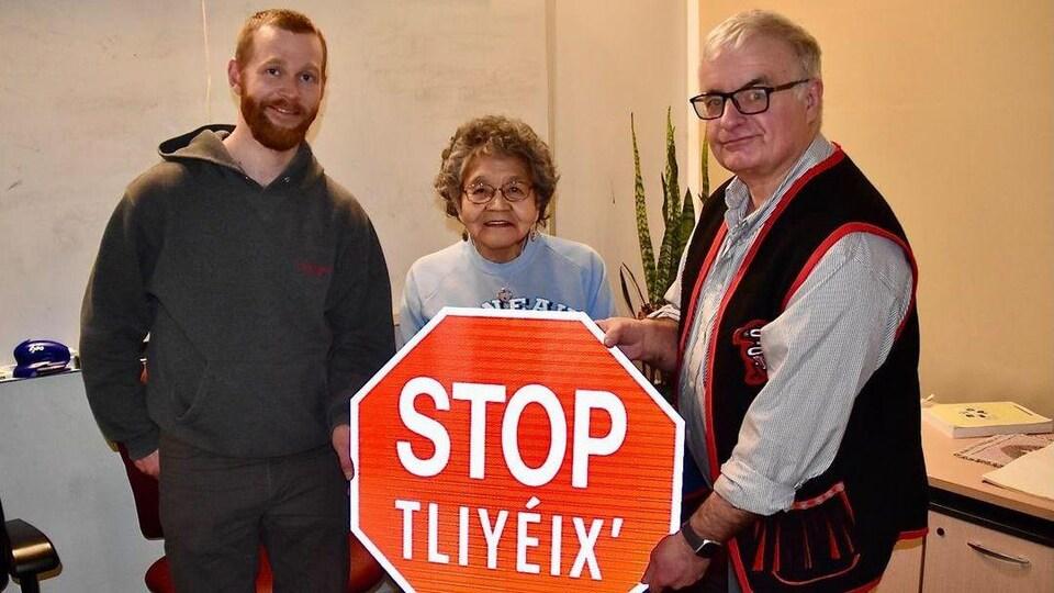 Trois personnes tiennent un panneau routier « arrêt » en anglais et tlingit.