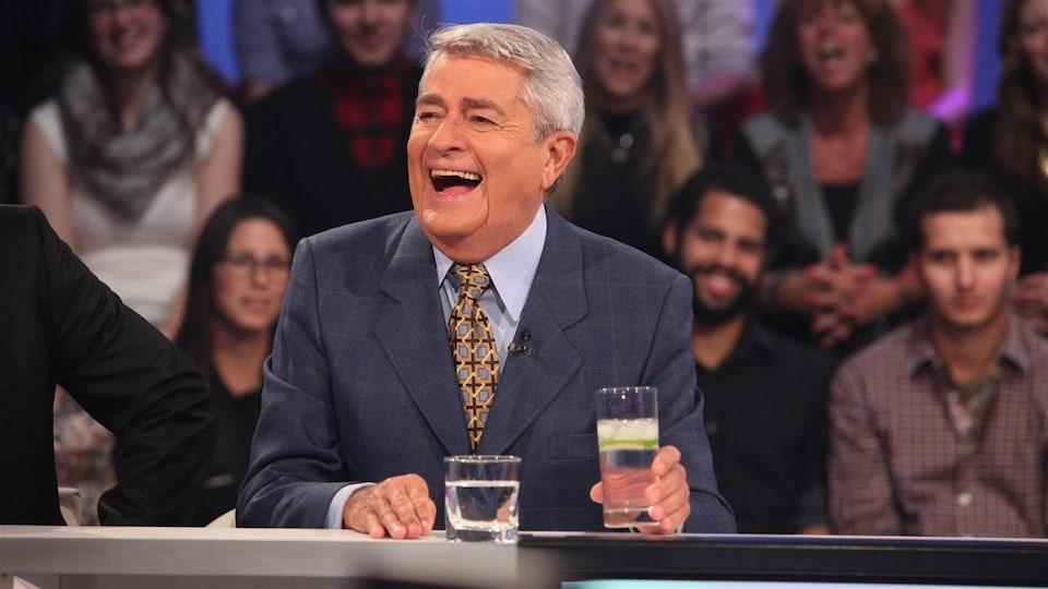 L'homme est assis dans un studio de télé et rit en regardant sur le côté. Le public est assis derrière lui.