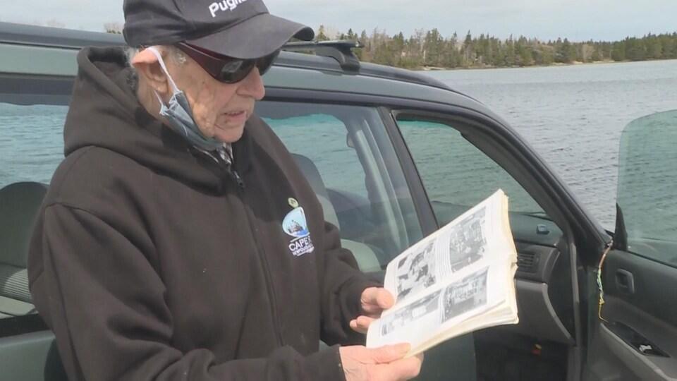 Un homme tient dans ses mains un livre avec des photographies historiques.