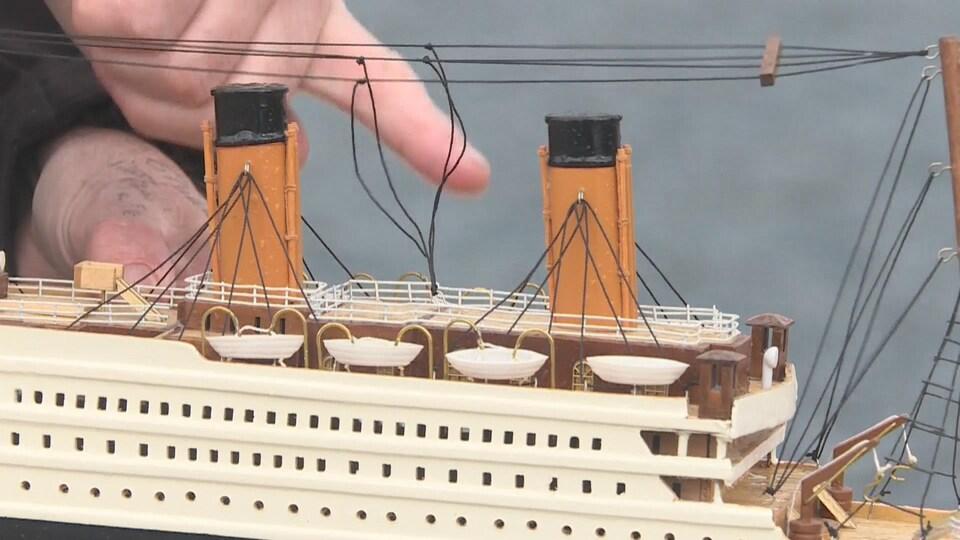 Photo d'un modèle réduit du Titanic. Larry Dailey pointe du doigt l'endroit approximatif où se trouve la salle contenant le télégraphe de Marconi, en dessous du pont supérieur.