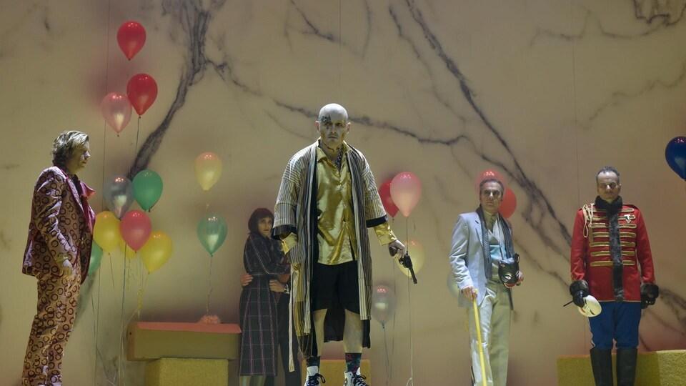 Plusieurs personnages en habits de fête se sentent menacés dans la pièce de théâtre L'idiot au Théâtre du Nouveau Monde.