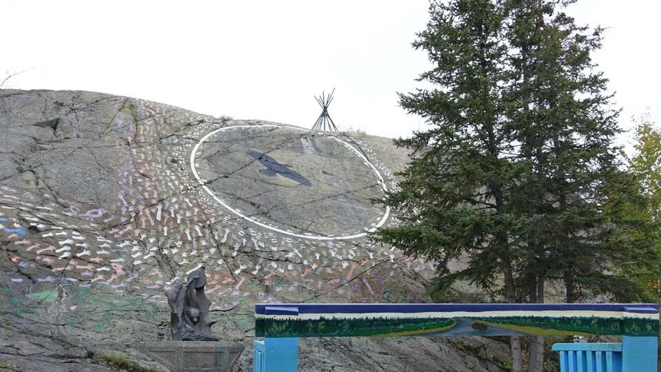 parc avec murale sur un rocher présentant des empreintes de mains