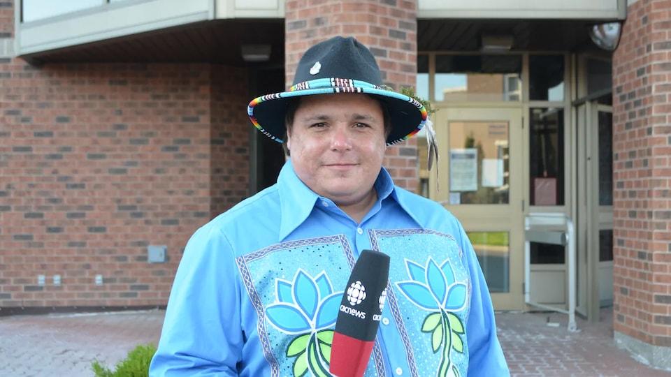 Todd Genno tient un micro devant un bâtiment.