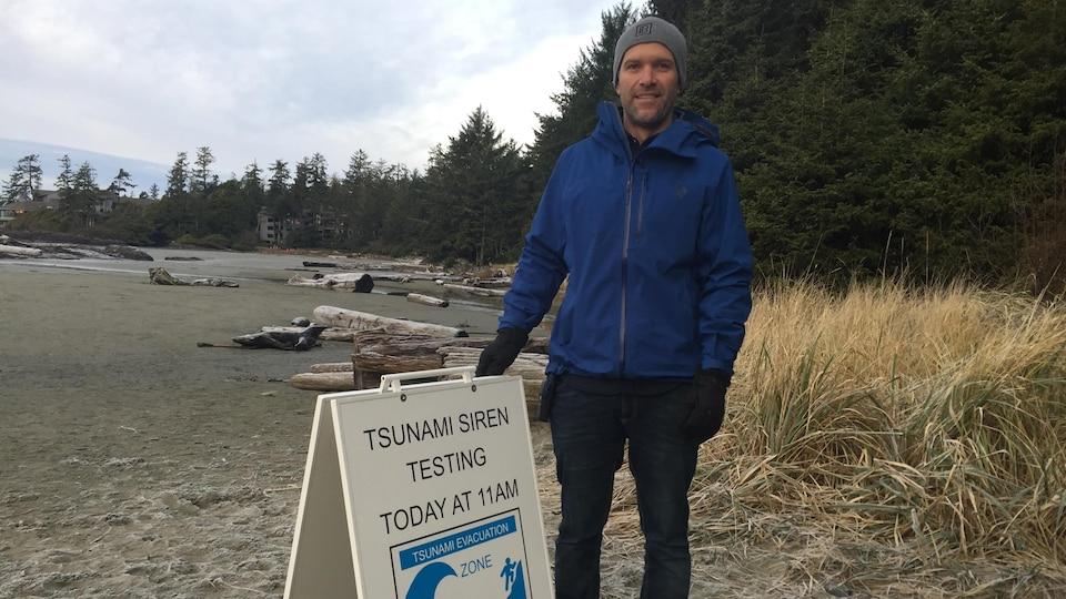 Un homme dans la trentaine habillé avec un manteau et une tuque est debout sur une plage et tient une affiche indiquant test de sirène pour tsunami à 11h aujourd'hui.