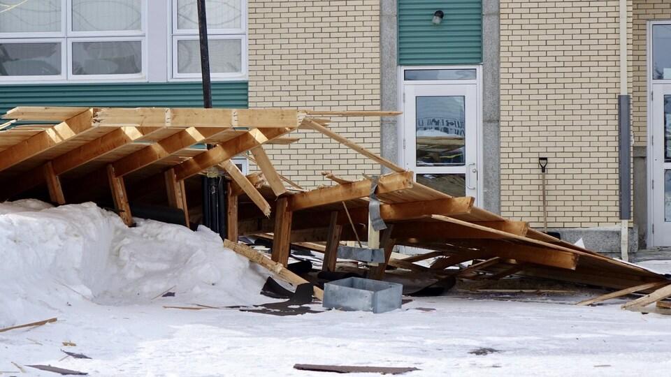 Des fermes de toit tombés par terre devant l'école.