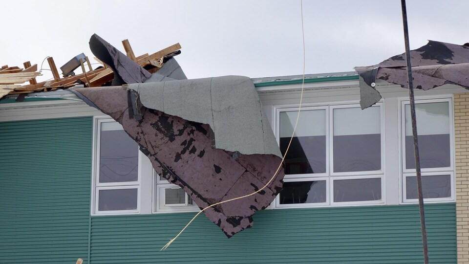 Des bardeaux du toit de l'école pendent le long du mur.