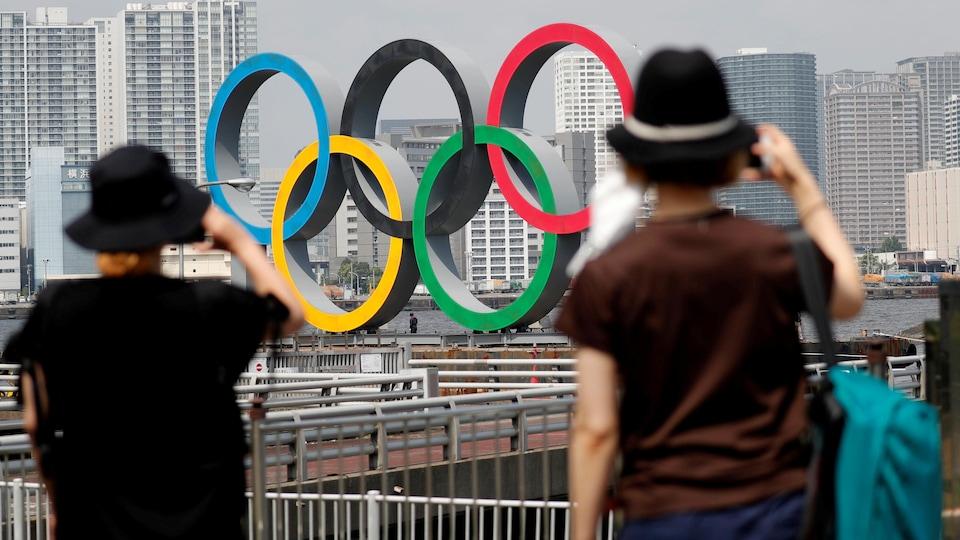 Deux personnes photographient les anneaux olympiques.