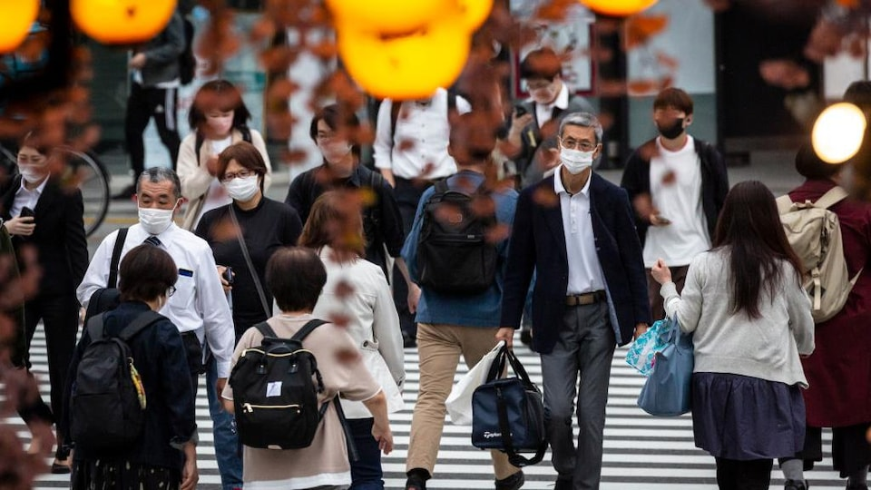 Des gens portant des masques se promènent dans la rue.