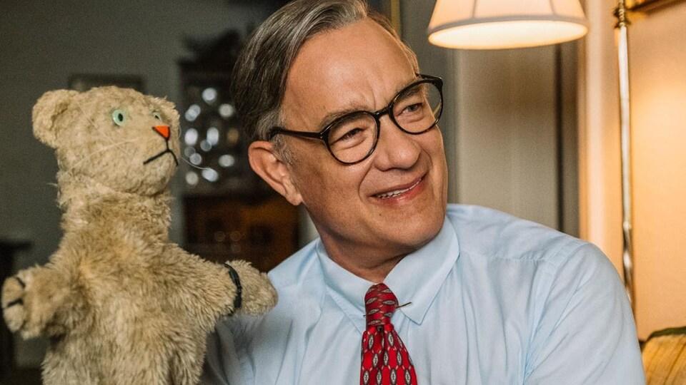 Tom Hanks incarne Mr. Rogers de la célèbre émission pour enfants. Il tient une marionnette dans ses mains.
