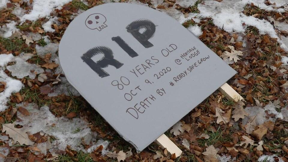 Une pierre tombale en carton avec un crâne.