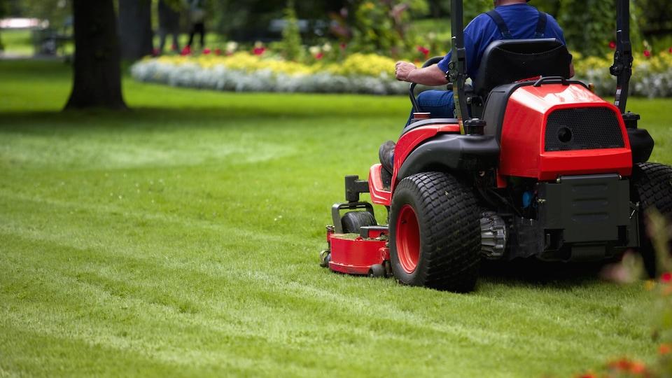Un homme conduit une tondeuse autoportée sur une pelouse.