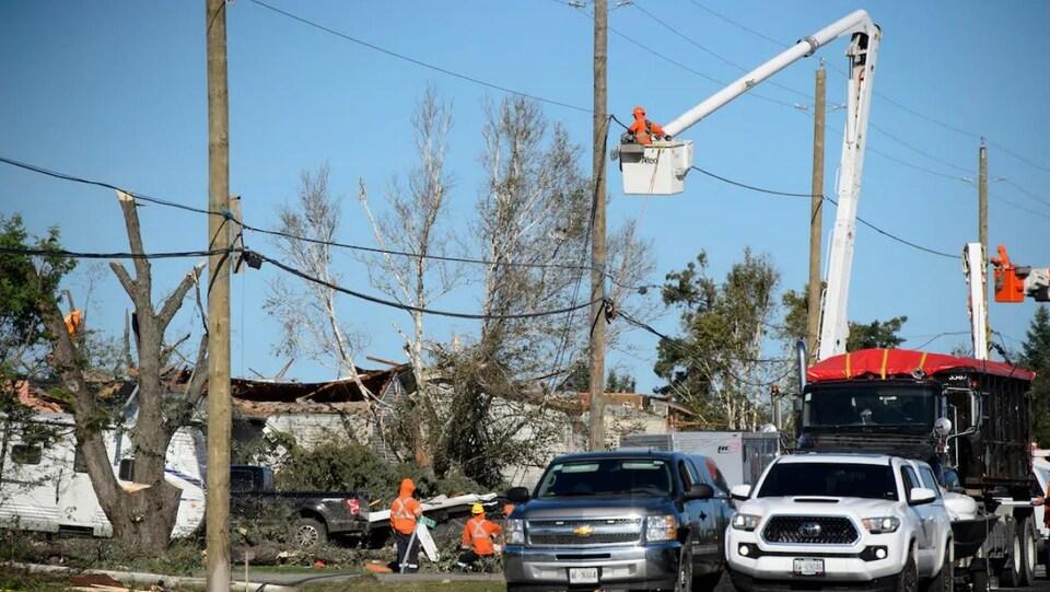 Des camions et des travailleurs devants des débris de maisons.