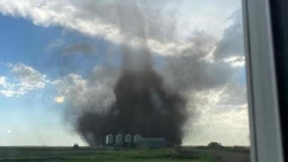 Photo prise derrière une fenêtre d'une tornade proche d'une exploitation agricole.