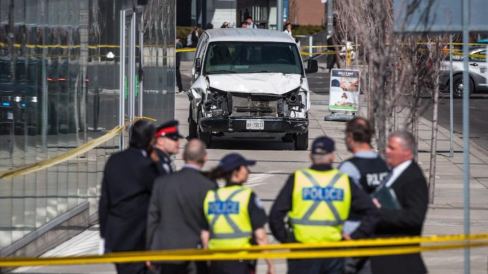 Des policiers devant une fourgonnette blanche.