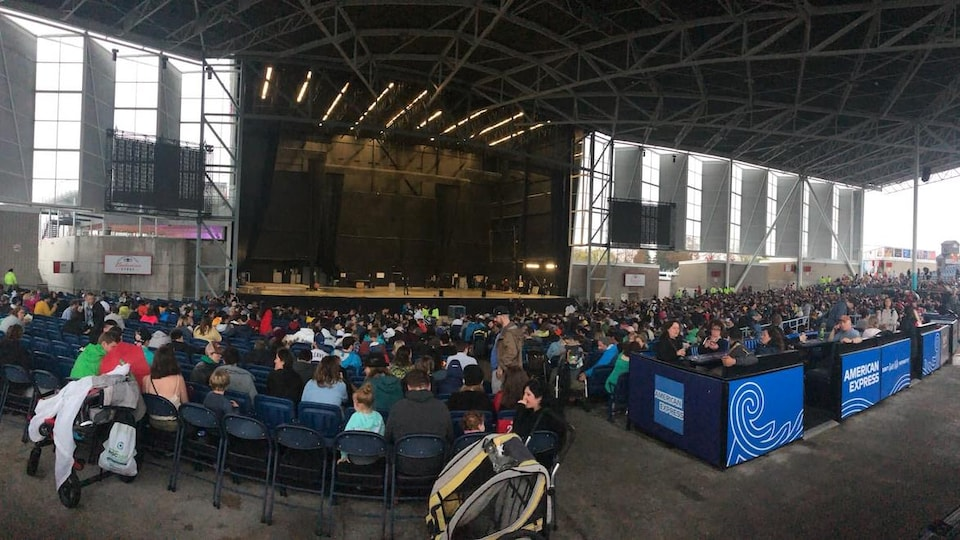 Des centaines de personnes sont assises sous un abris devant une scène.