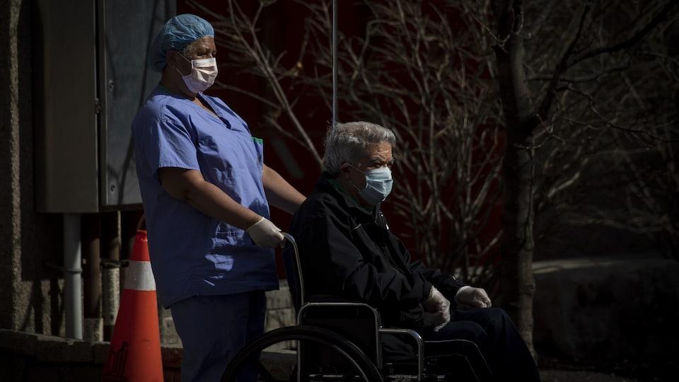 Une préposée aux bénéficiaires aide au transfert d'un résident à l'extérieur d'un centre de soins de longue durée de Toronto.