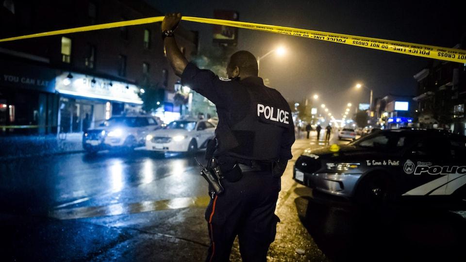 Un policier en uniforme soulève un ruban, qui sert à fermer un secteur lorsque les policiers érigent un périmètre de sécurité. La photographie a été prise le soir, car il fait sombre et seuls les néons et lampadaires illuminent la scène.