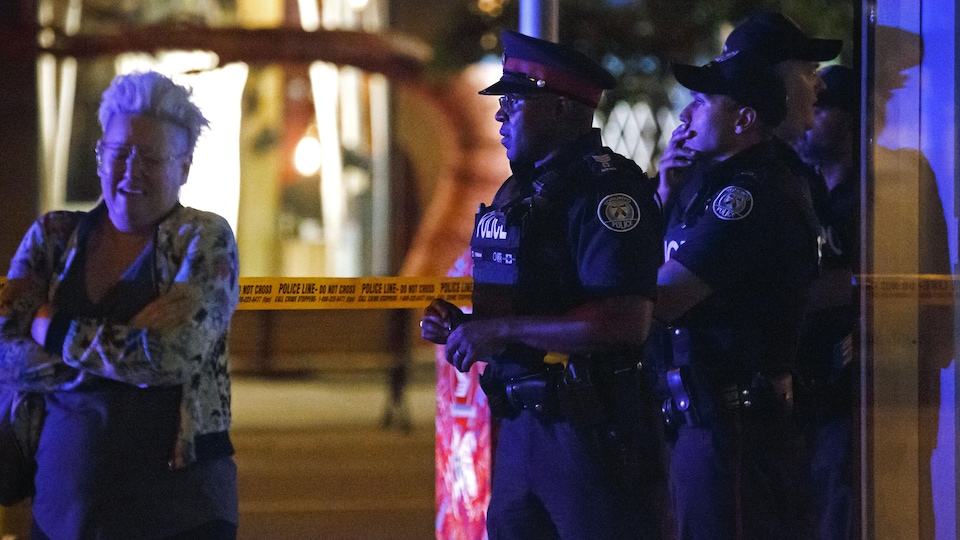 Des policiers en uniforme regardent droit devant eux, l'air penseur, alors qu'une femme aux cheveux courts pleure près d'eux. La photographie a été prise le soir ou la nuit, puisqu'il fait sombre.