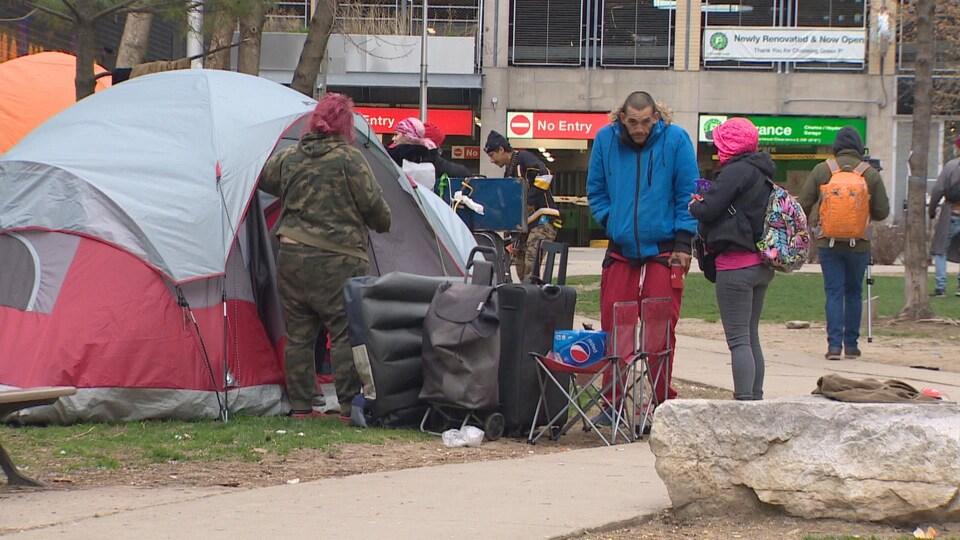 Des sans-abri près d'une tente érigée dans un parc.