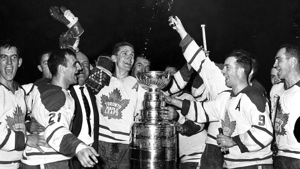 Des joueurs de hockey célèbrent autour de la coupe en 1962.
