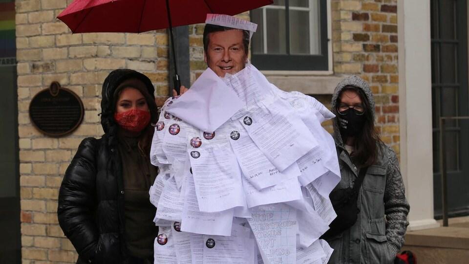 Un carton à l'effigie du maire avec deux femmes