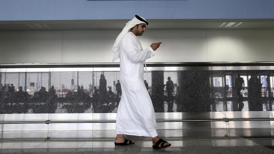 Un homme regarde son téléphone aux Émirats arabes unis.