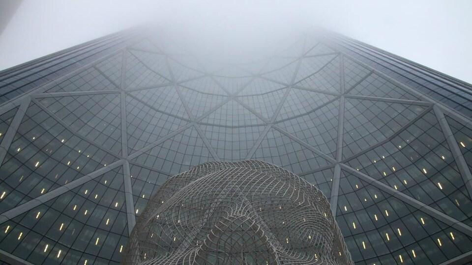 La tour Bow prise en contre-plongée, avec une statue au premier plan et du brouillard au sommet.
