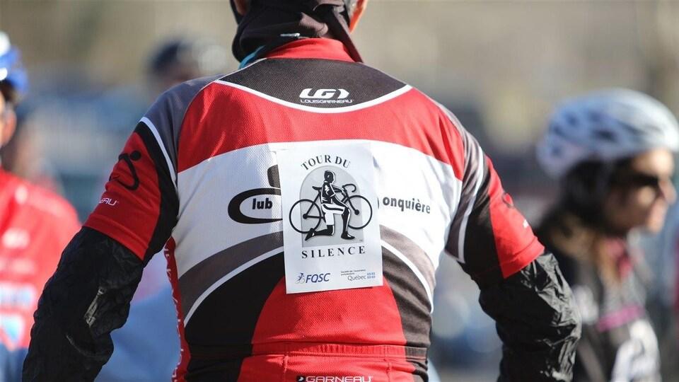 L'affiche du Tour du Silence accrochée dans le dos d'un cycliste.