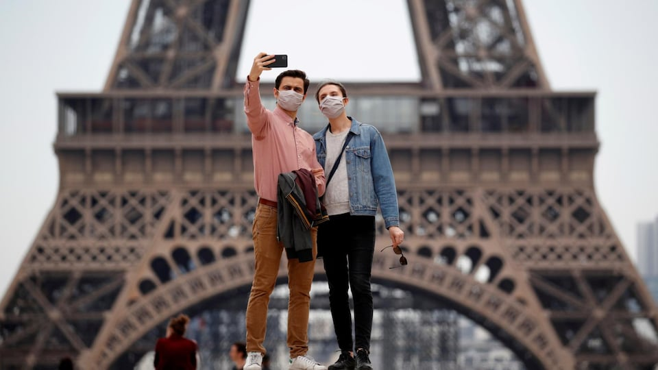 Un couple prend un autoportrait devant le tour Eiffel.